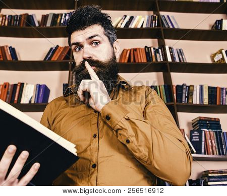 Man On Busy Face Reading Book Shows Silence Gesture, Bookshelves On Background. Education And Scienc