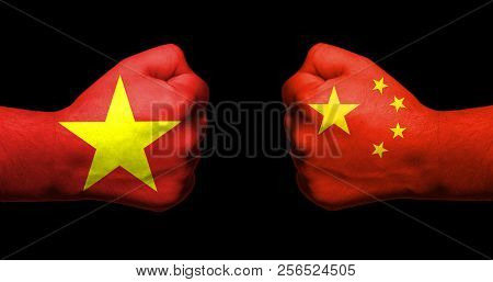 Flags Of Vietnam And China Painted On Two Clenched Fists Facing Each Other On Black Background/vietn