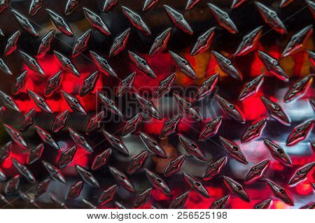 Close Up Of Stainless Steel Sheet With Diamond Plate Pattern And Reflecting Red Lights / Metallic Ba