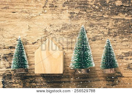 Top View Of Mini Christmas Tree Wood Home Toy On Rustic Wooden Table With Snow Fall.winter Holiday S