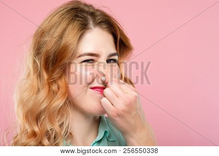 bad rancid smell or terrible odor concept. woman holding her nose and grimacing. emotion expression and reaction concept. young beautiful blond girl portrait on pink background. poster