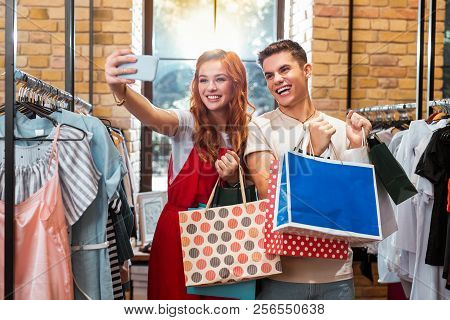 Excited Couple Taking Selfies While Doing Shopping Together