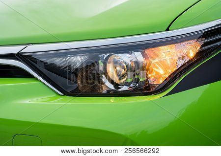 Front Headlight On A Modern Green Car. Low Beam And Turn Signal Or Blinker Lit.