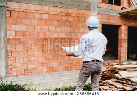 Construction Engineer With Plans, Working On Building Construction Site. Brick Walls, Infrastructure