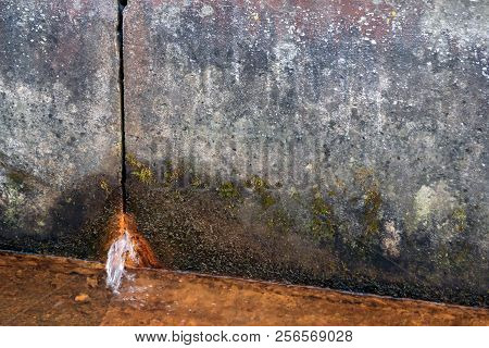 Two Concrete Slabs Of Dirty Gray Color In Spots, Rusty Water Flows From The Hole From Below, In The