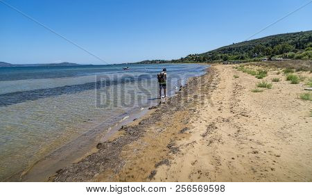 Young Man With Backpack Walking On A Dirty Beach