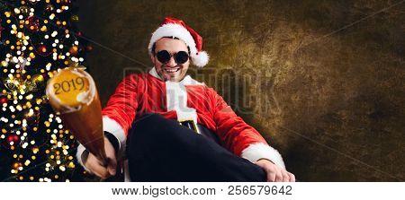 Bad Santa with 2018 baseball bat sitting indoors near Christmas or New Year fir tree