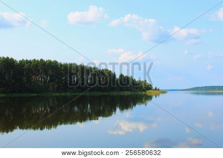 Beautiful lake. Beautiful green forest. Lake in summer forest. Forest and sky clouds reflected in the lake. Beautiful Russian nature lake. Summer landscape.