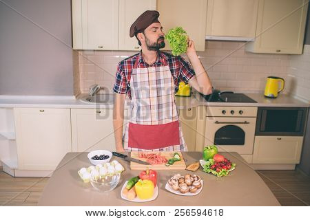 Bearded Man Stands And Smells Leaves Of Letuce. He Keeps Eyes Closed. Man Is Serious And Concentrate