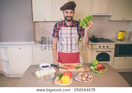 Happy And Positive Chief Stands In Kitchen And Looks On Camera. He Smiles. Young Man Holds Letuce In