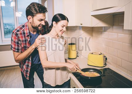 Positive Couple Stands In Kitchen. She Holds Pen Of Pan. Girl Cooks Omlet. Guy Stands Behind Her And