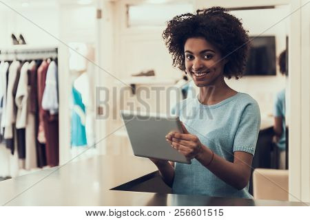 Female Employee Using Tablet At Work In Store. Beautiful Smiling African Woman With Afro Hairstyle U
