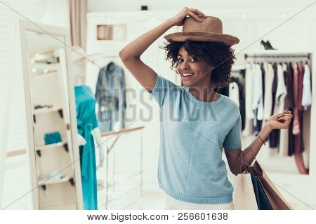 Smiling Young Woman Trying On New Hat In Store. Happy Beautiful Black Girl Choosing Hat To Buy In Bo