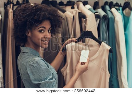 Smiling Young Woman Shopping In Clothing Store. Happy Beautiful Black Girl Choosing Clothes To Buy I