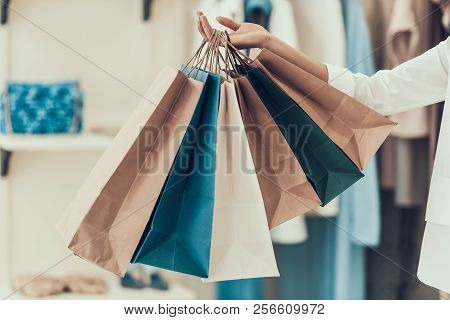 Closeup Young Girl Holding Shopping Bags In Store. Close Up Of Black Girl Holding Shopping Paper Bag