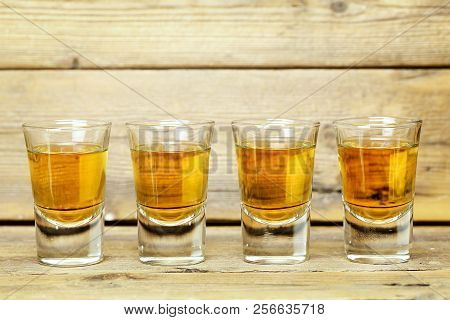Closeup Of Four Whiskey Shots On Weathered Wooden Planks