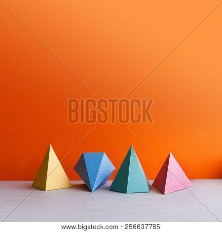 Platonic Solid Geometric Figures. Three-dimensional Pyramid Rectangular Triangle Objects On Orange G