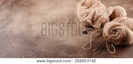 Hanks of woolen brown threads, knitting needles and a knitting pattern on a brown background poster