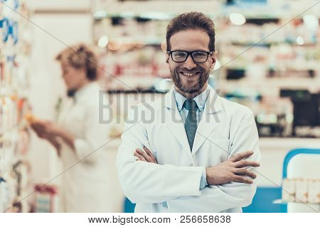 Portrait Smiling Pharmacist Working In Drugstore. Male Pharmacist Wearing White Coat And Glasses Sta