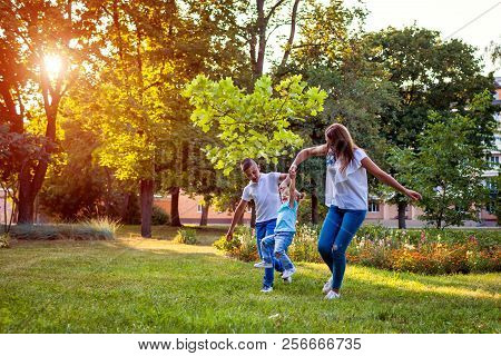 Happy Family Spending Time Outdoors Playing In Park. Mom Having Fun With Two Kids. Family Values