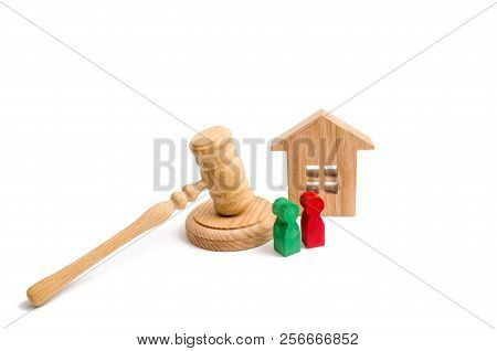 Wooden Apartment House With Keys And A Judge Hammer On A White Background. The Concept Of The Trial