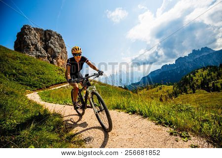 Woman cycling in Cortina d'Ampezzo, stunning Cinque Torri and Tofana in background. Riding MTB trail. South Tyrol province of Italy, Dolomites. poster