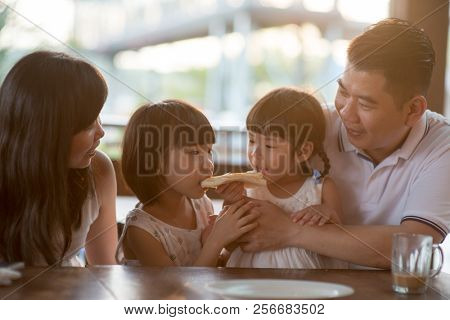 Adorable children eating and sharing butter toast at cafe. Asian family outdoor lifestyle with natural light.