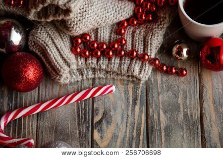 festive christmas decor background. seasonal design with holiday adornments and embellishments. knitted sweater shiny balls beads and candy cane on wooden backdrop. poster