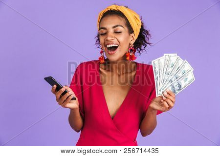 Image of brunette woman 20s in hair band smiling and holding fan of money in dollar banknotes with mobile phone in hands isolated over violet background