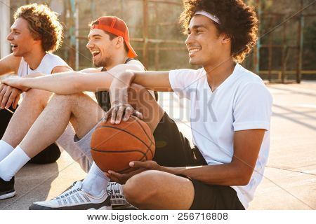 Photo of young professional basketball players sitting at playground outdoor and watching game during summer sunny day