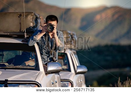 Young Asian Male Traveler And Photographer Sitting On The Car Window Taking Photo On Road Trip In Na