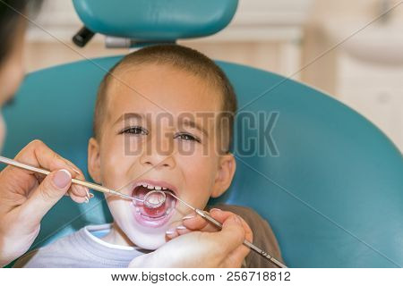 Pediatric Dentist Examining A Little Boys Teeth In The Dentists Chair At The Dental Clinic. Dentist