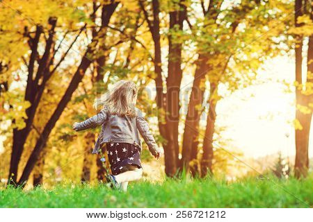 Happy Child Girl Running In Autumn Park. Little Girl Having Fun In Autumn. Happy Childhood. Stylish