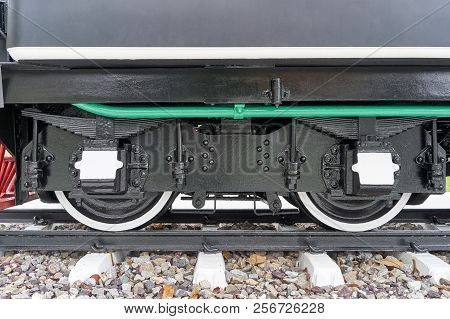Black And White Wheel Of Train With Shock Absorber And Green Pipe With Railway On Rocky.