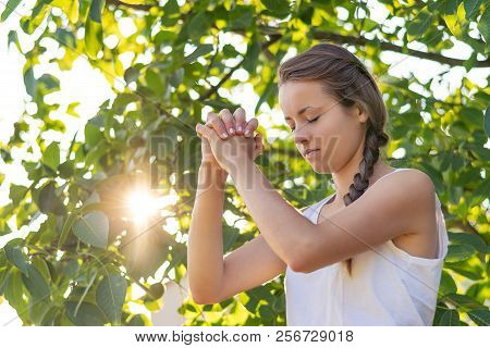 Christian Worship And Praise. A Young Woman Is Praying In The Early Morning With Sun In The Backgrou