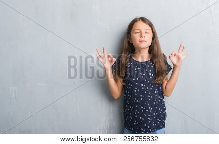 Young hispanic kid over grunge grey wall relax and smiling with eyes closed doing meditation gesture with fingers. Yoga concept.