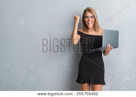 Beautiful young business woman over grunge grey wall using computer laptop screaming proud and celebrating victory and success very excited, cheering emotion