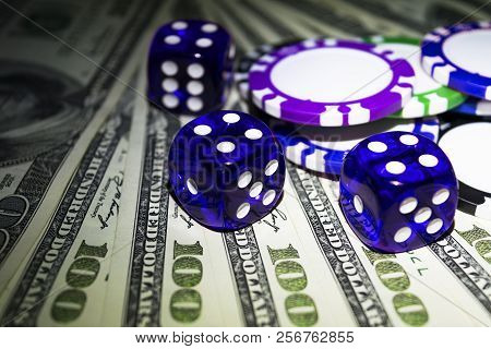 Stack Of Poker Chips With Blue Dice Rolls On A Dollar Bills, Money. Poker Table At The Casino. Poker
