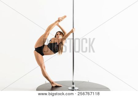 Full Length Of An Attractive Pole Dancer Doing Split Around The Pole In Studio