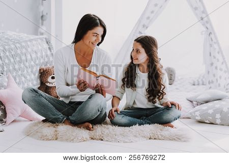 Young Mother Reading Book To Little Daughter. Beautiful Smiling Woman Sitting On Carpet Reading To C