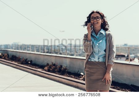 Young Smiling Woman Talking On Cellphone Outdoor. Portrait Of Beautiful Business Woman Wearing Glass