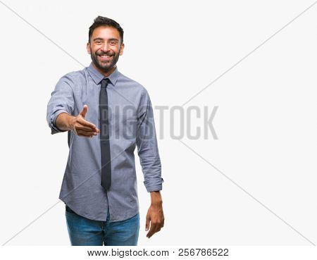 Adult hispanic business man over isolated background smiling friendly offering handshake as greeting and welcoming. Successful business.