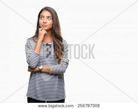 Young beautiful arab woman wearing sunglasses over isolated background with hand on chin thinking about question, pensive expression. Smiling with thoughtful face. Doubt concept.