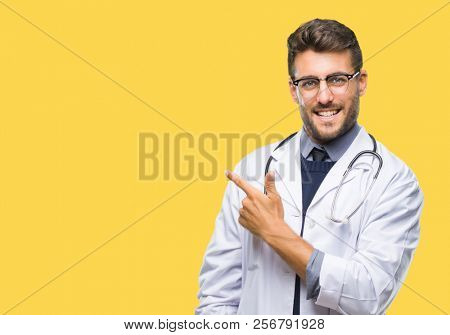 Young handsome doctor man over isolated background cheerful with a smile of face pointing with hand and finger up to the side with happy and natural expression on face looking at the camera.