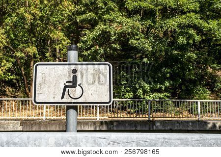 Dirty Handicap Sign With A Wheel Chair And Green Nature In The Background