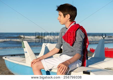 Young boy sitting on catamaran at the summer beach. Cute spectacled smiling happy 12 years old boy at seaside. Kid's outdoor portrait over seaside.