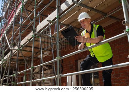 Male builder foreman, construction worker or architect on site holding a clipboard and drinking a mug of coffee or tea