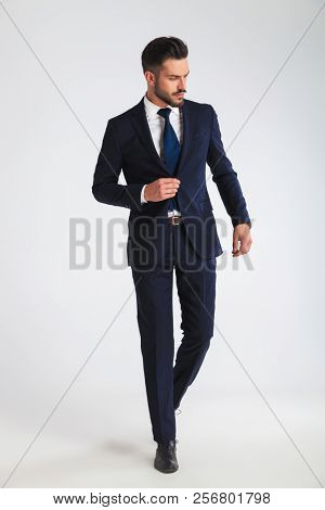 82fc7b9b315 young businessman walking on light grey background and buttoning his navy  suit while looking down to