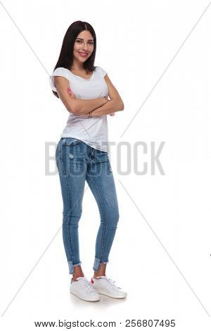 confident brunette woman wearing a white t-shirt and jeans standing with arms crossed on white background, full body picture
