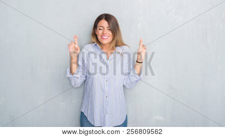 Young adult woman over grey grunge wall wearing fashion business outfit smiling crossing fingers with hope and eyes closed. Luck and superstitious concept.